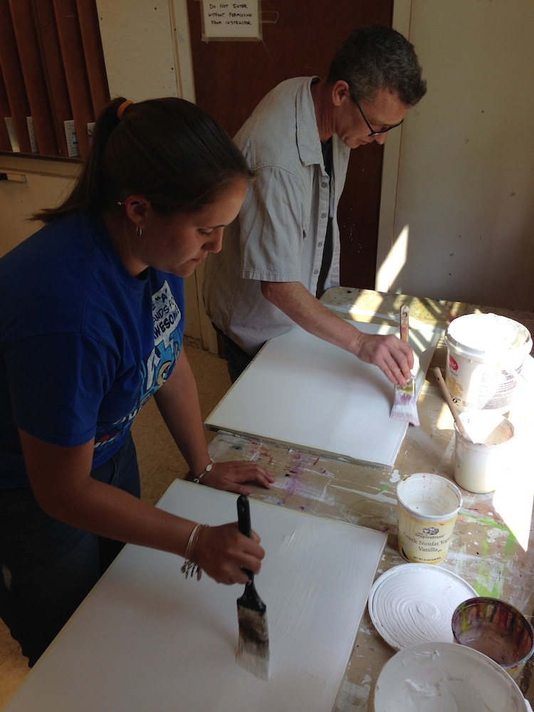 Students putting on gesso